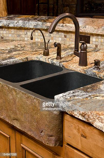 Close up kitchen sink with stone counter
