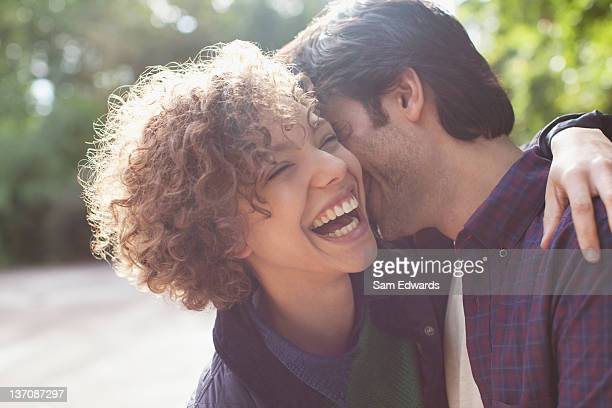 Close up laughing couple hugging
