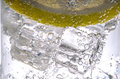 Close up lemon slice splashing into soda water