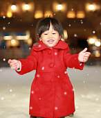 Close up Little girl wearing a red jacket has a fun in snow, Winter time.