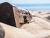 close up locked chest in the sand on the beach