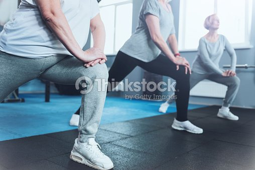 Close up look on retired women lunging at fitness club : Stock Photo