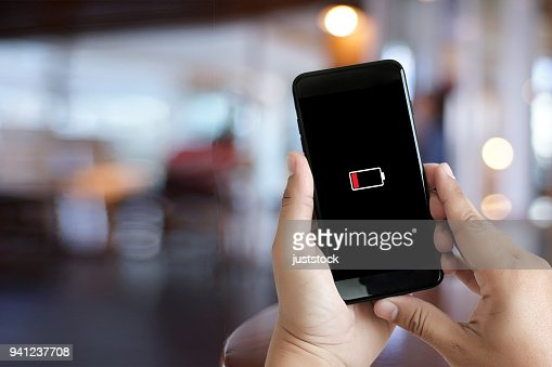 Close up man hands using smart phone battery low charged battery screen : Stock Photo