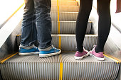 Close up Men wear jeans and woman on escalator to up