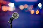 Close up microphone on stage in concert hall, bokeh light background