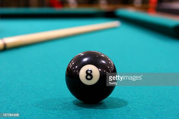 Close up of 8 ball on green felted pool table