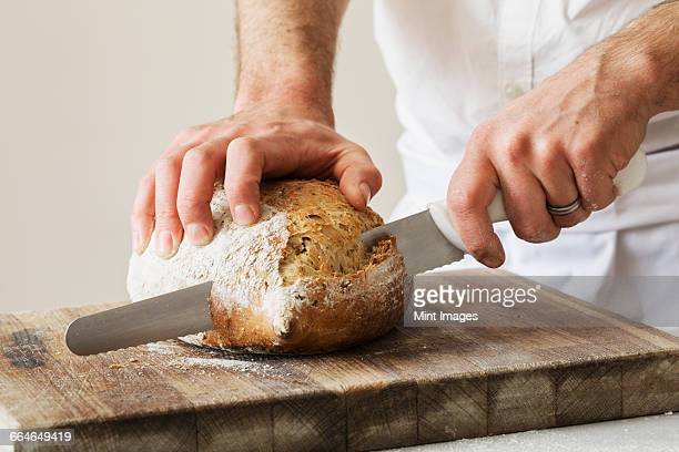 Close up of a baker slicing a freshly baked loaf of bread with a bread knife.
