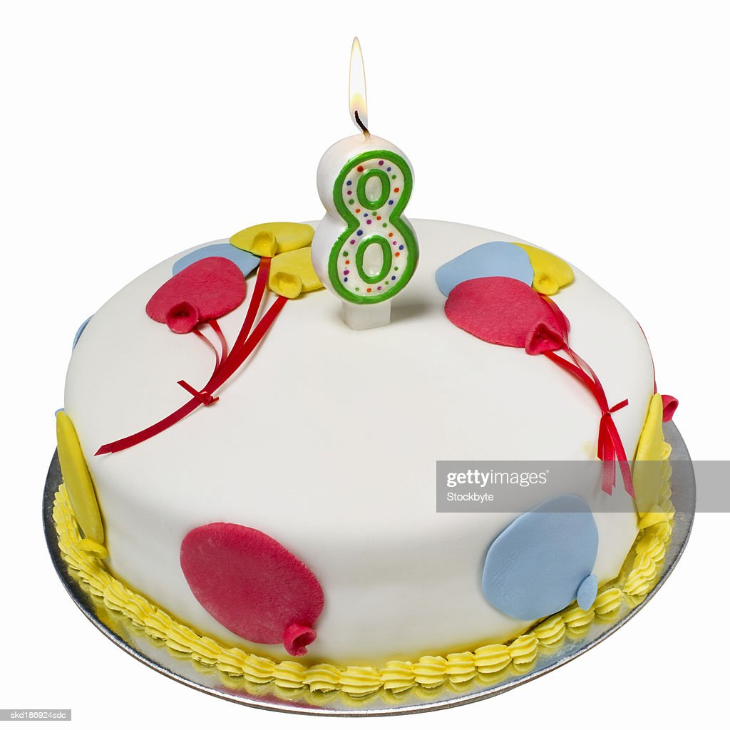 Close up of a birthday cake with an eight candle on top : Stock Photo
