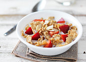 close up of a bowl of cereal and milk with almons and strawvberries on rustic wooden table