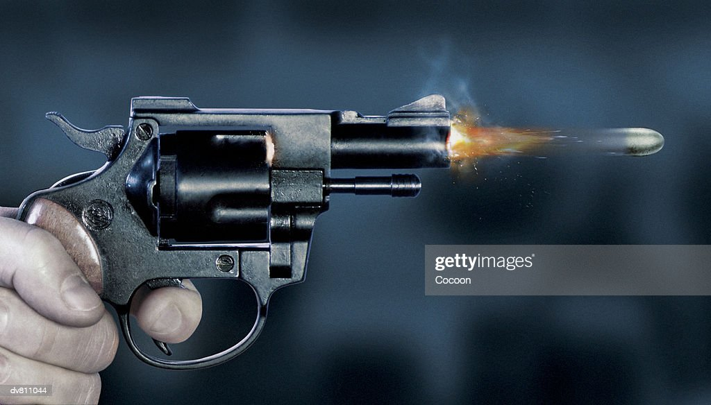 Close Up of a Bullet Coming Out of a Gun : Stock Photo