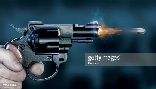 Close Up of a Bullet Coming Out of a Gun