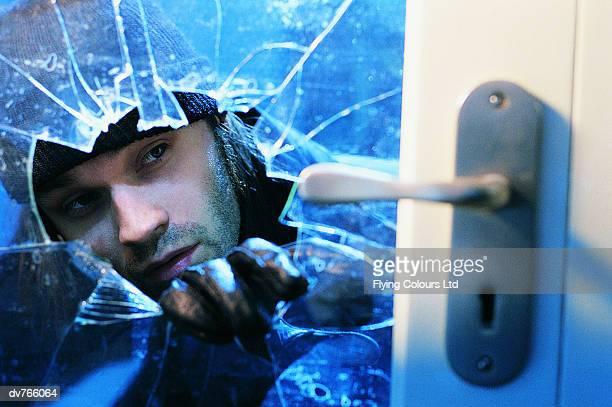Close Up of a Burglar Looking at a Door Handle Through a Hole in a Door Window