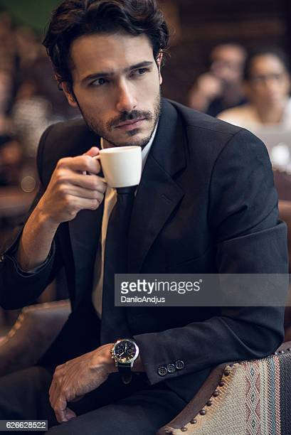 close up of a businessman drinking coffee after work