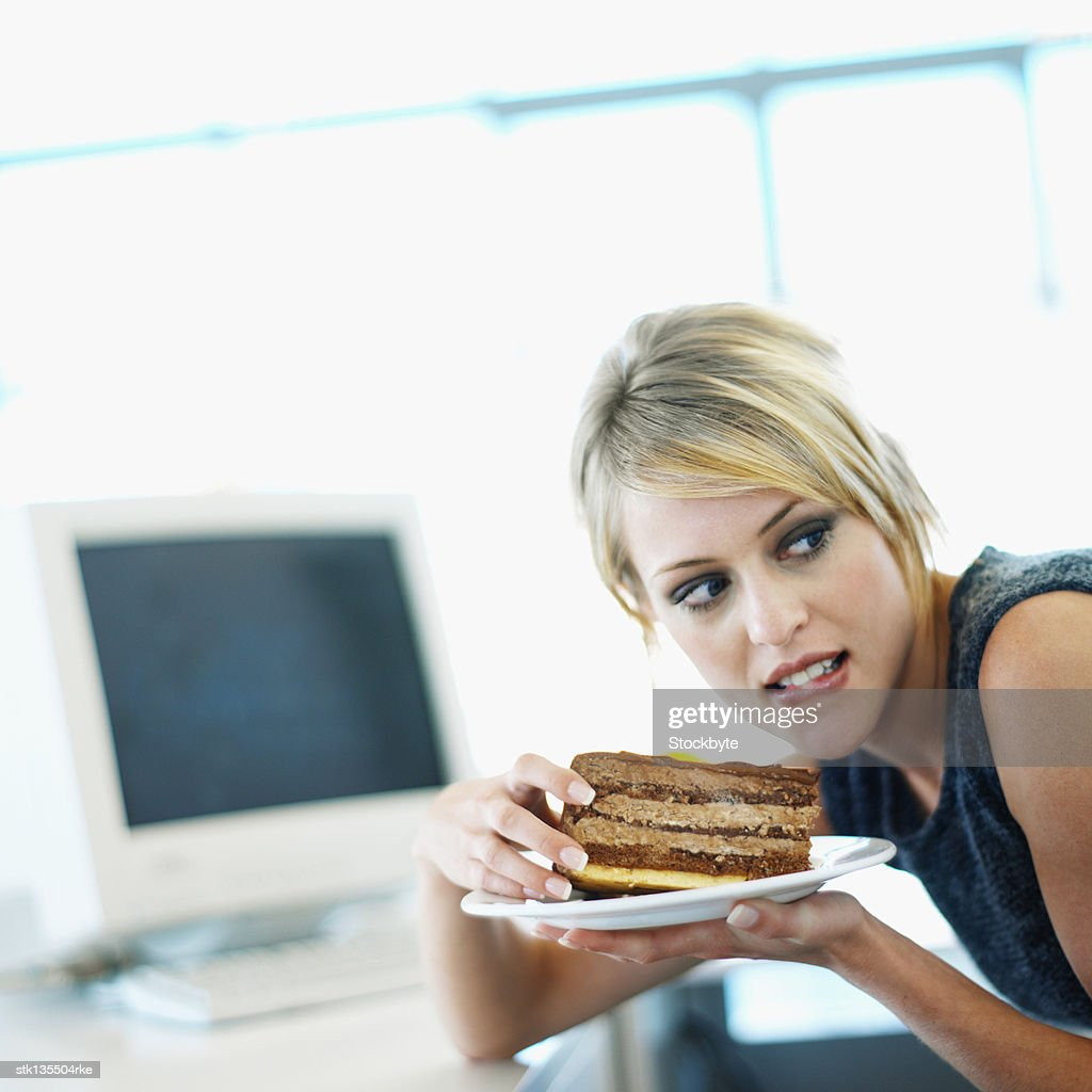 close up of a businesswoman eating a piece of chocolate cake and watchful : Stock Photo