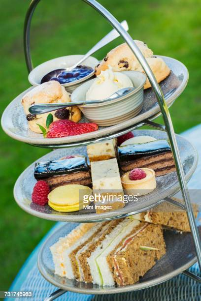 Close up of a cake stand with a selection of cakes and sandwiches, traditional afternoon tea.
