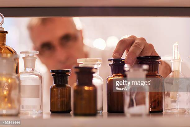 Close up of a chemist choosing the right bottle.
