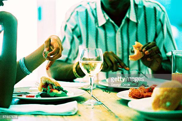 close up of a couple eating at the table with faces hidden