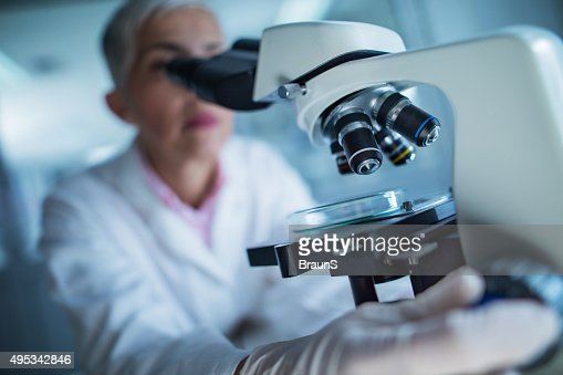 Close up of a doctor using microscope.