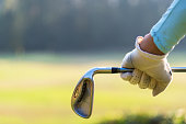 Close up of a female golfer holding an iron behind his body