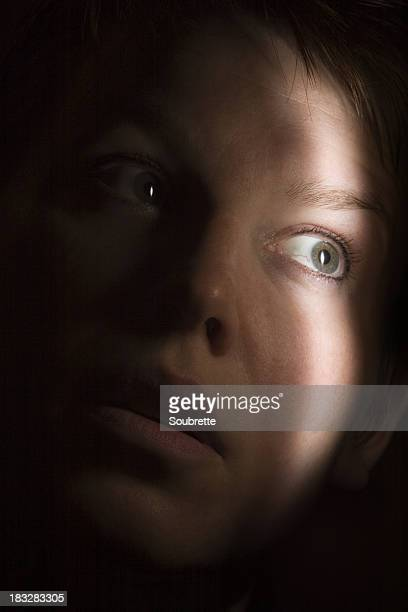 Close up of a frightened hiding woman's face