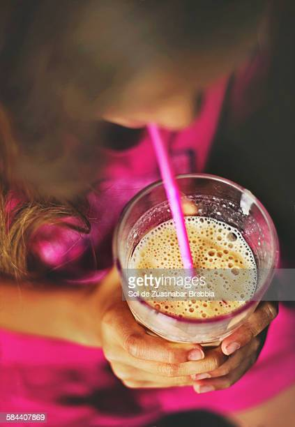 Close up of a fruit smoothie held in a girl' hands
