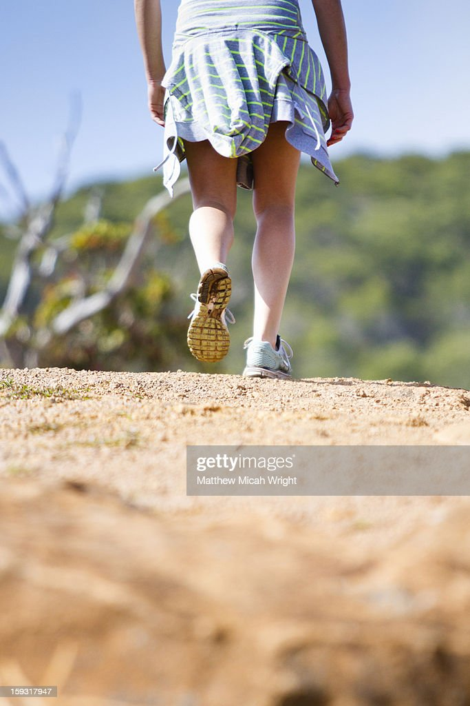 A close up of a girl hiking a dirt trail. : Stock Photo
