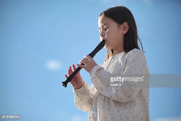 Close up of a girl playing recorder outdoor.