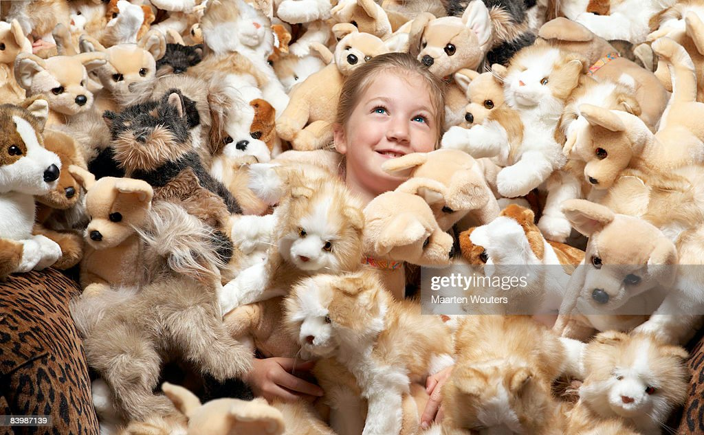 Close up of a girl surrounded by stuffed toys : Stock Photo