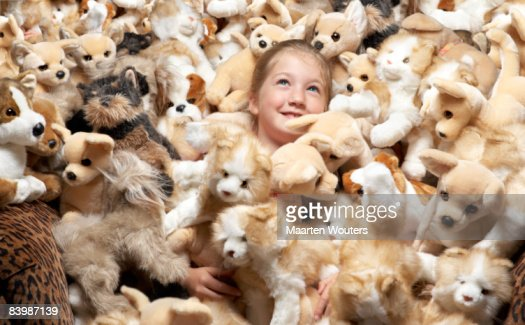 Close up of a girl surrounded by stuffed toys
