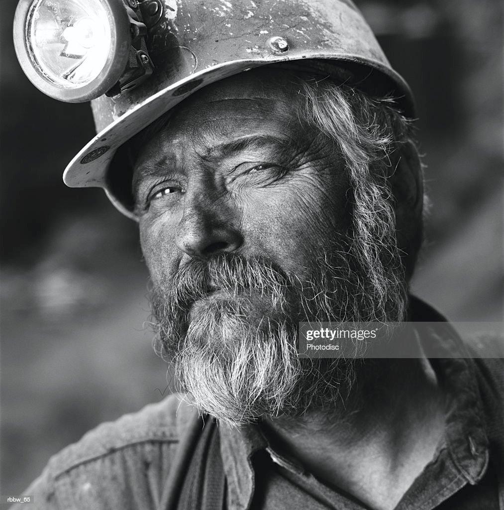 A close up of a gruff caucasian coal miner