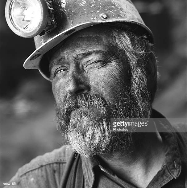 A close up of a gruff caucasian coal miner