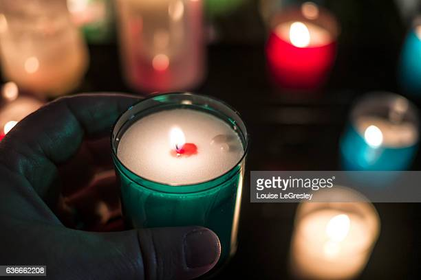 close up of a hand holding a votive candle with other candles in the background