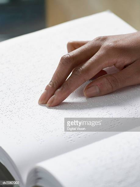 Close Up of a Hand Touching a Braille Book