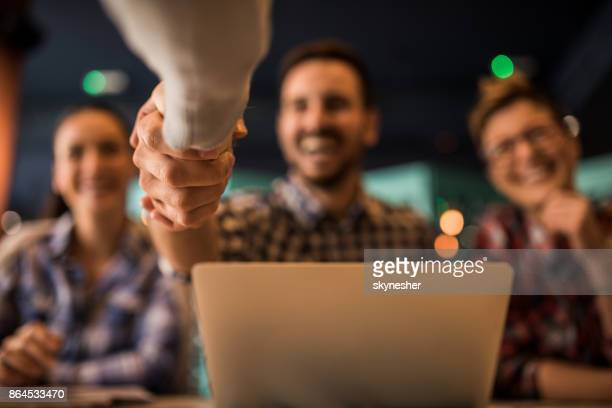 Close up of a handshake during a job interview.
