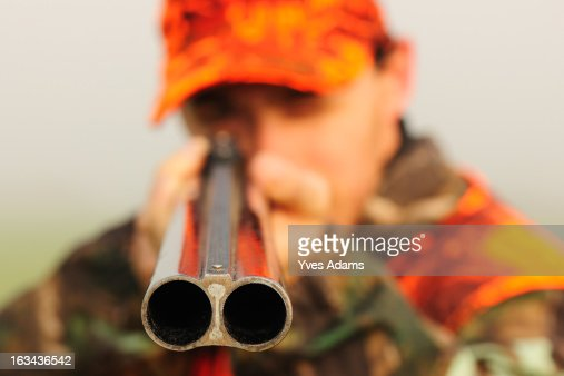 Close up of a hunter aiming his shotgun : Stock Photo