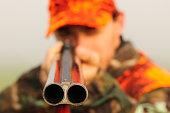 Close up of a hunter aiming his shotgun