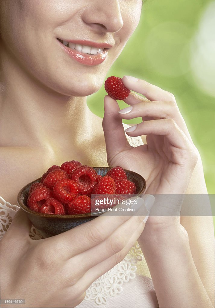 close up of a lady eating raspberries from a bowl : Stock Photo