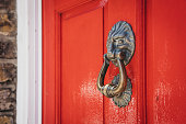 Close up of a lion's head door knocker on a bright red door of a typical British house.