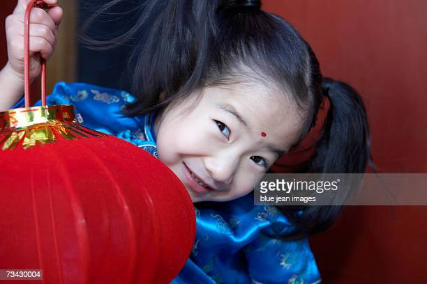 Close up of a little girl holding a lantern in the doorway of a traditional courtyard home decorated for the Chinese New Year.