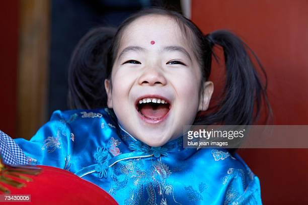 Close up of a little girl laughing as she holds a lantern in the doorway of a traditional courtyard home decorated for the Chinese New Year.