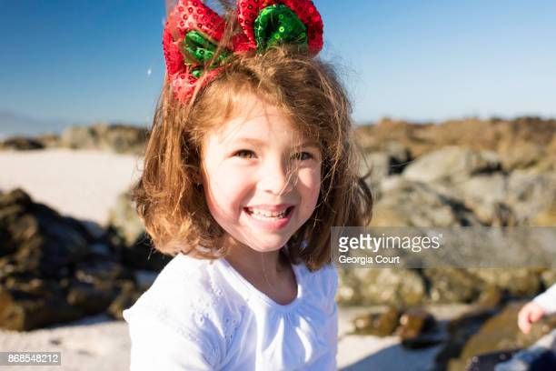 Close up of a little girl smiling to camera a pretty Christmas bow in her hair