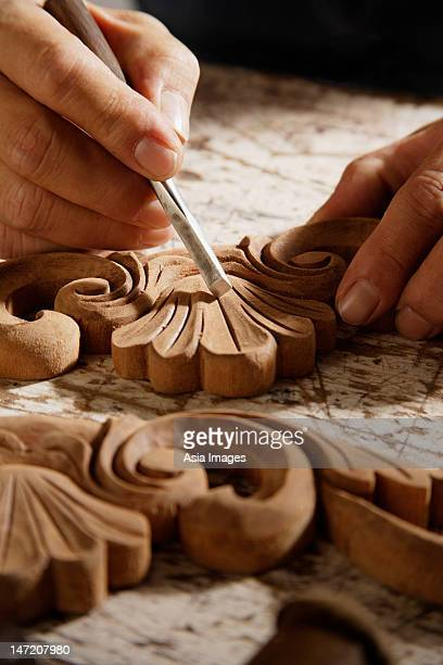 Close up of a man carving a piece of wood.