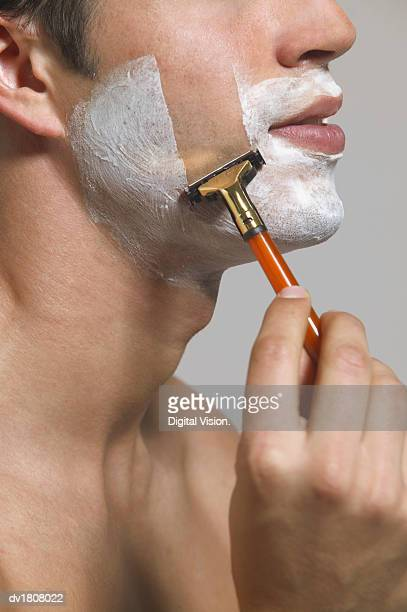 Close up of a man Holding a Razor and Shaving His Cheek