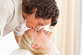 Close up of a man kissing his fiance on the forehead in their living room