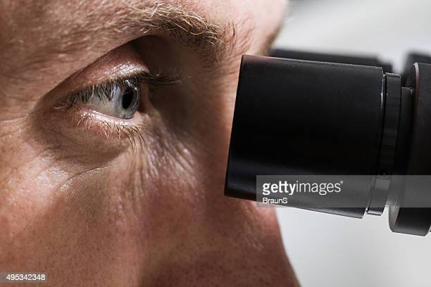 Close up of a man looking through a microscope.