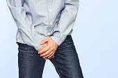 Close up of a man with hands holding his crotch on a light blue background. Urinary incontinence. Men's health. The pain from the blow in groin.