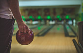 A man's hand holding bowling ball preparing to throw it on bowling lane
