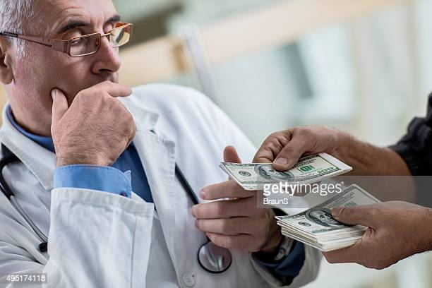Close up of a mature doctor receiving bribery.
