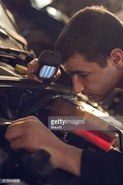 Close up of a mechanic examining an engine.