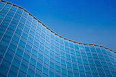 Close up of a modern architecture with blue sky background - glass building exterior